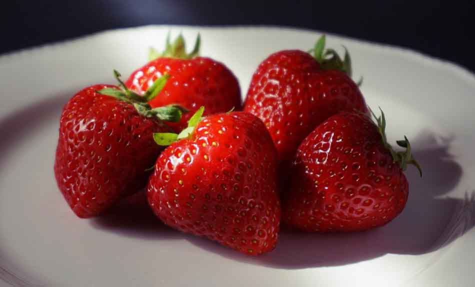 5 strawberries on a white plate